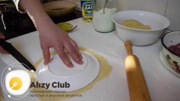 Берем десертную тарелку, кладем ее вверх дном на раскатанный пласт