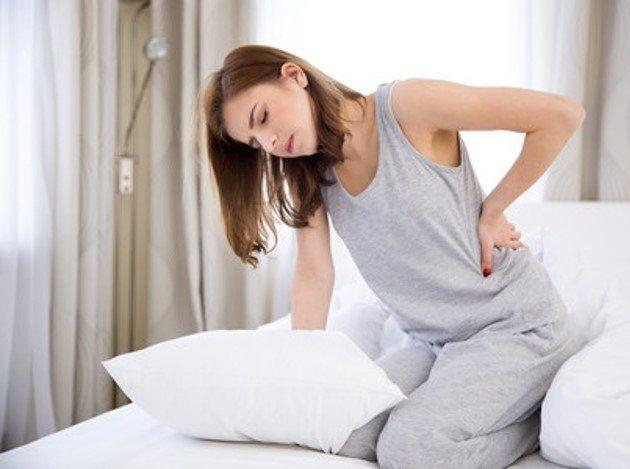 беременная женщина держит рукой подушку