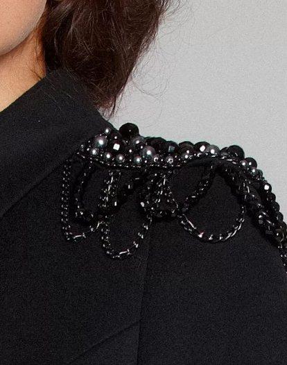 черное пальто украшено бусинами и стразами