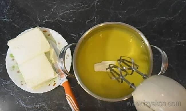 Чтобы приготовить самый вкусный крем для бисквитного торта со сгущенкой, добавляем в него масло и взбиваем.