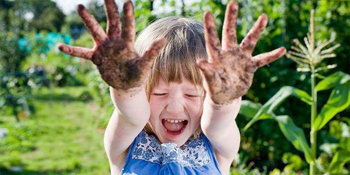 Девочка показывает грязные ладошки