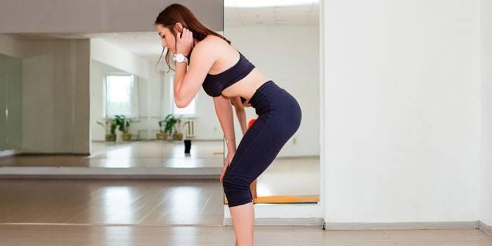 Девушка делает упражнение вакуум в положении стоя