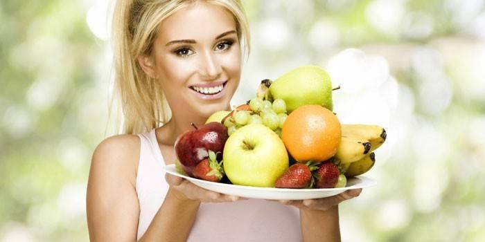 Девушка держит блюдо с фруктами и ягодами