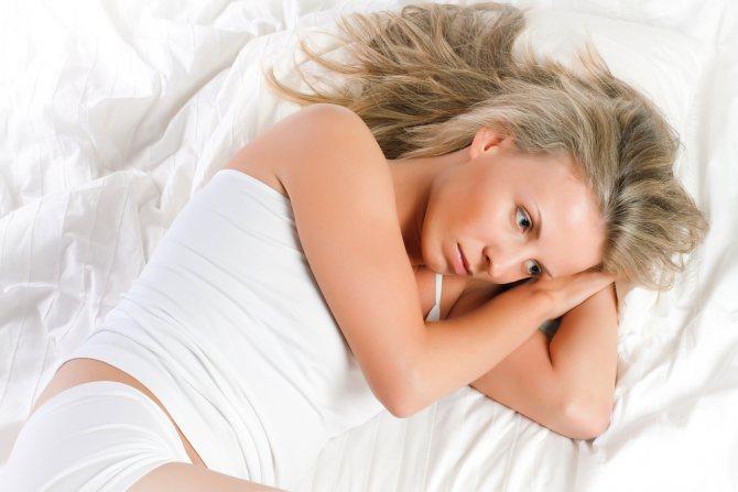 девушка лежит на белой простыни