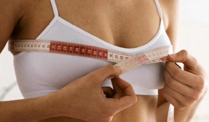 Девушка меряет грудь сантиметром