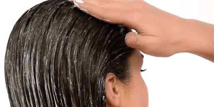 Девушка наносит маску для волос