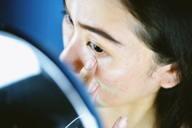 Девушка перед зеркалом наносит на очищенную кожу праймер или базу для макияжа.