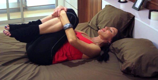 девушка поджимает колени лёжа на кровати