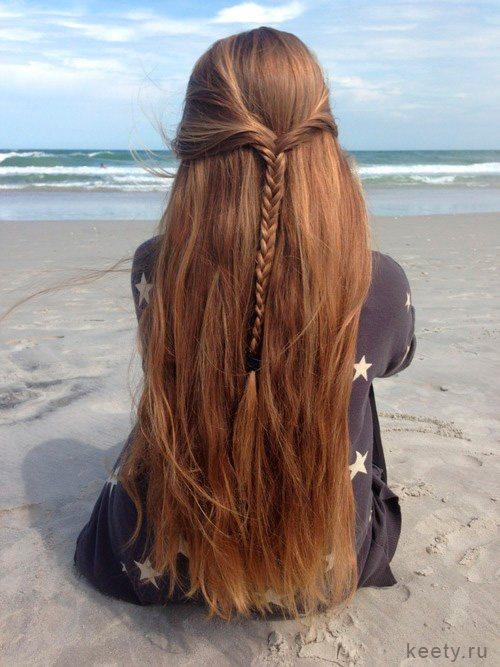 Девушка сидит на песке с распущенными волосами