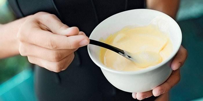 Девушка смешивает кефир с лимоном в тарелочке