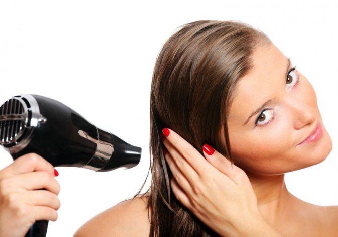 Девушка сушит феном волосы
