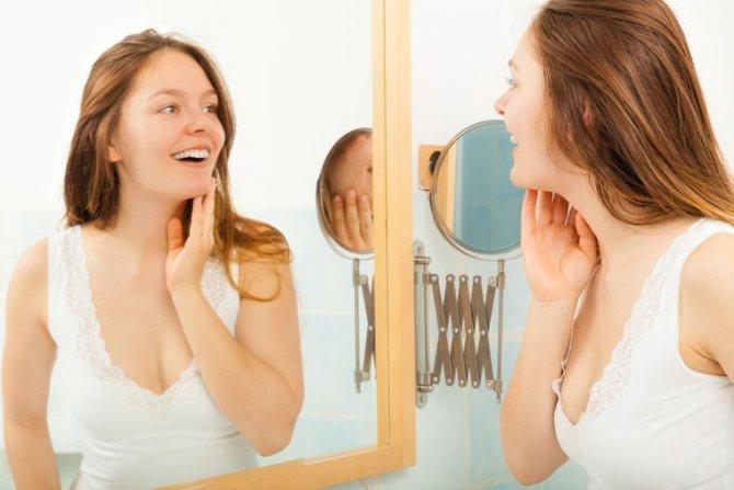 девушка улыбается перед зеркалом