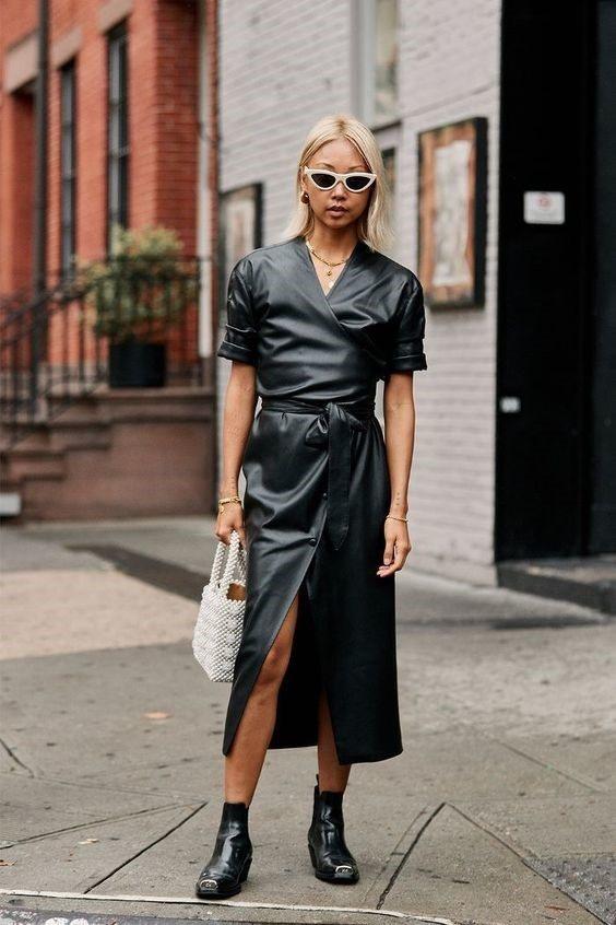 Девушка в черном кожаном платье с поясом, черные ботильоны на плоской подошве и жемчужная сумка
