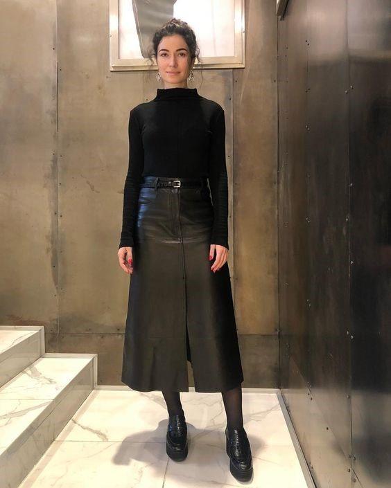 Девушка в кожаной юбке миди, черная водолазка и ботинки на платформе