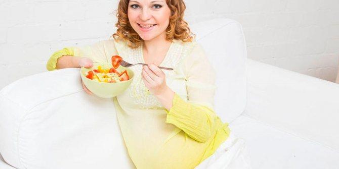 Девушка в положении ест салат
