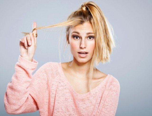 девушка завивает волосы на палец