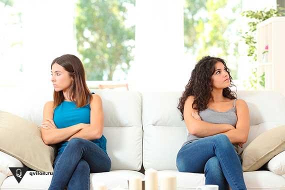 девушки смотрят в разные стороны сидя на одном диване