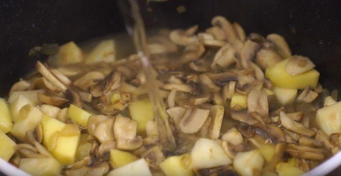 Добавление лука с моркови и шампиньоны в кастрюлю с полуготовым картофелем