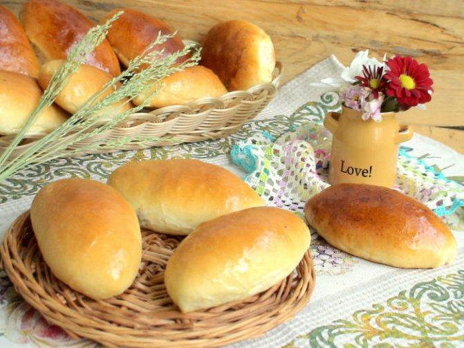домашние пирожки с сыром и яйцом на столе и в корзине