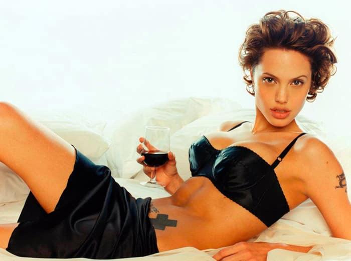 Джоли лежит на диване полуобнаженная с бокалом вина в руке