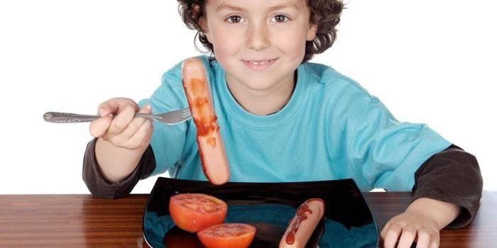 Мальчик ест сосиски