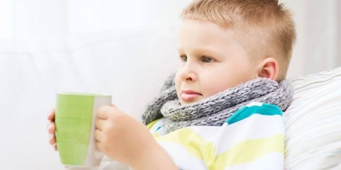Мальчик в шарфе с чашкой в руках