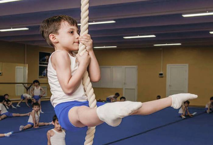 Мальчик занимается спортивной гимнастикой