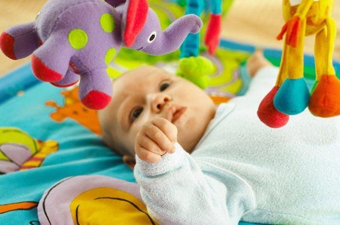 малыш смотрит на игрушки