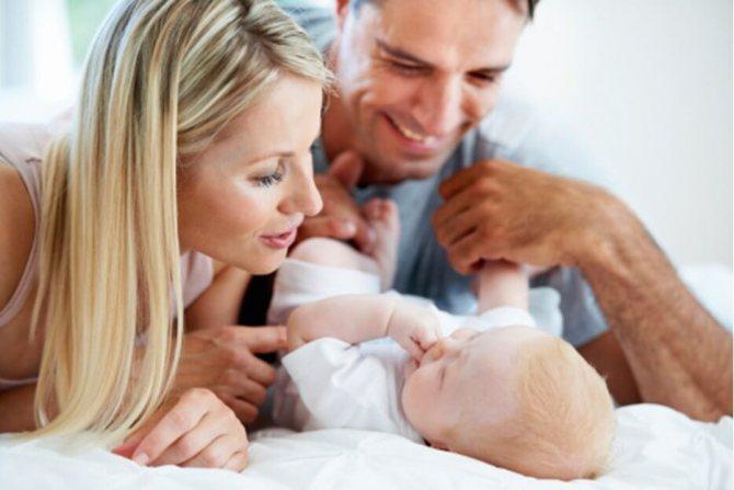 Мама и папа над малышом