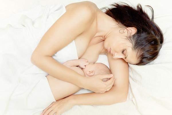 Мать кормит новорожденного молоком