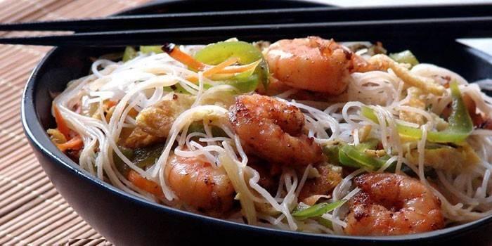 Морепродукты с рисовой лапшой на тарелке