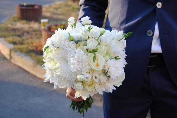 Мужчина дарит белые розы