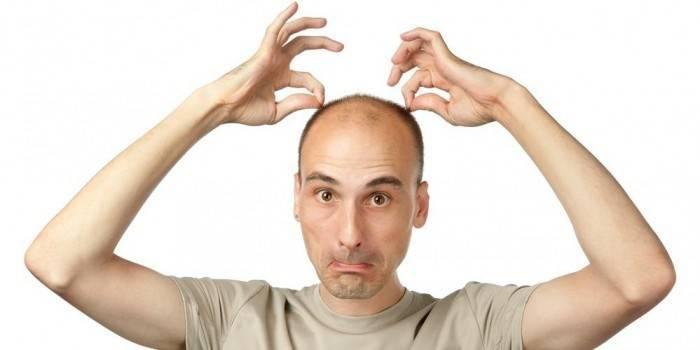 Мужчина держится руками за волосы на голове
