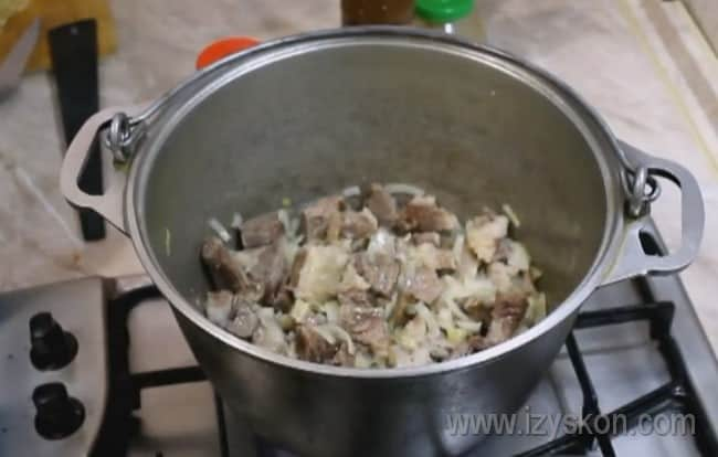 Нарезанное кусочками мясо добавляем к луку и продолжаем готовить заправку для супа харчо из говядины.