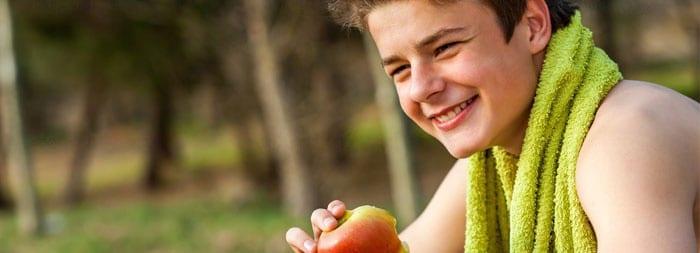 Подросток ест яблоко