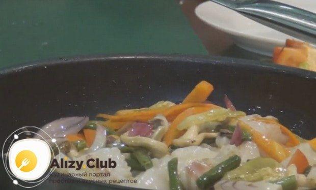 Поверх овощей выкладываем кусочки рыбы и перемешиваем.