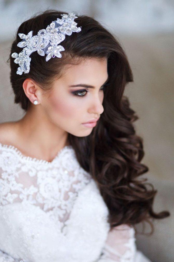 Прическа на один бок для невесты с украшением