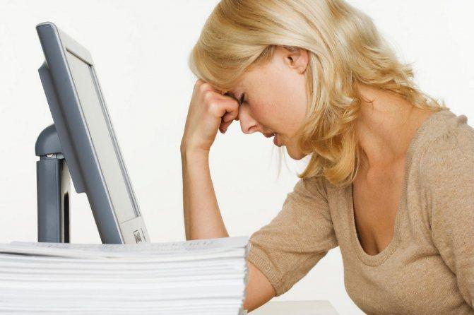 Расстроенная девушка облокотилась на кулак возле монитора за стопкой бумаги