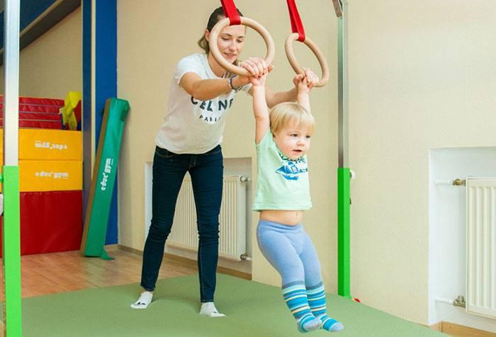 Ребенок с тренером в спортзале
