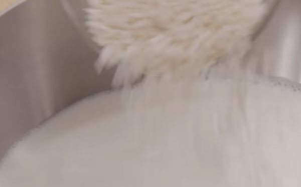 Рис всыпают в кастрюлю с молоком