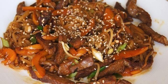 Рисовая лапша с кусочками свинины, кунжутом и овощами