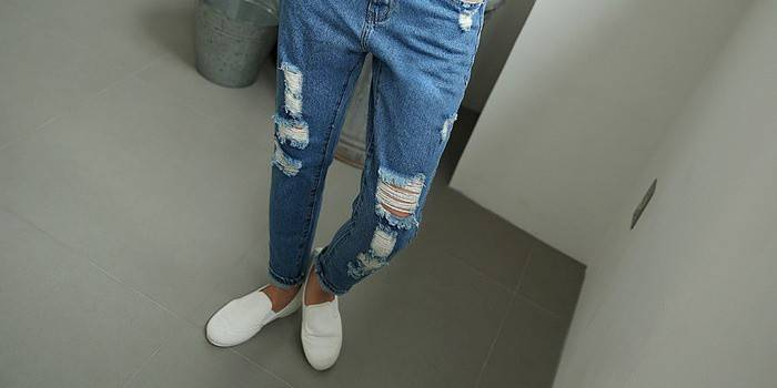 Рваные и потертые джинсы на девушке