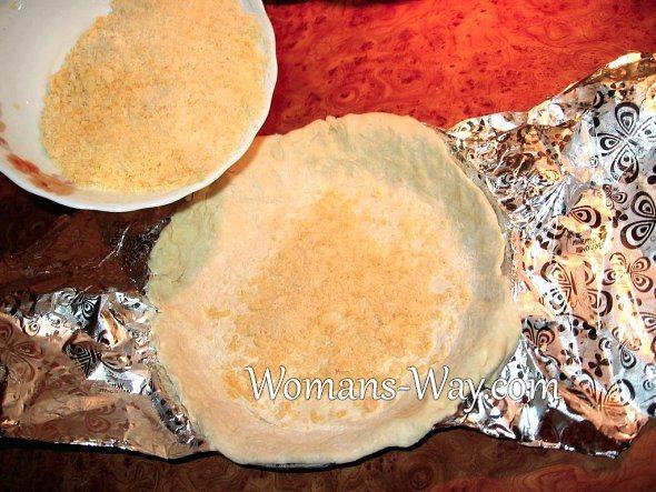 Слой измельченного сыра на раскатанном тесте для пиццы