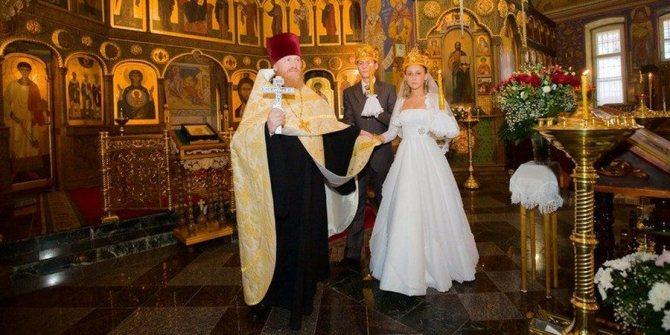Служитель церкви обводит пару вокруг аналоя трижды