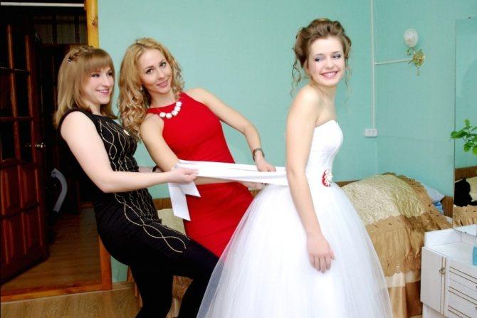 Свидетельница одевает платье невесте