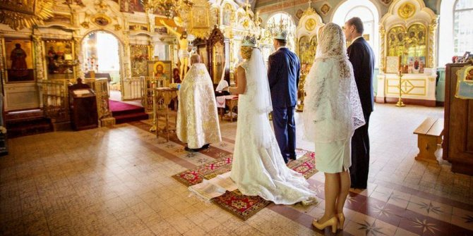 Священнослужитель проводит мужа и жену в центр храма
