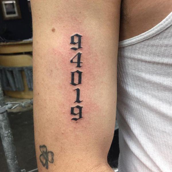 Татуировка цифры на плече парня