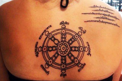 Татуировка колеса на спине у женщины