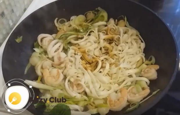 Теперь выкладываем в сковороду капусту, порей и добавляем лапшу.