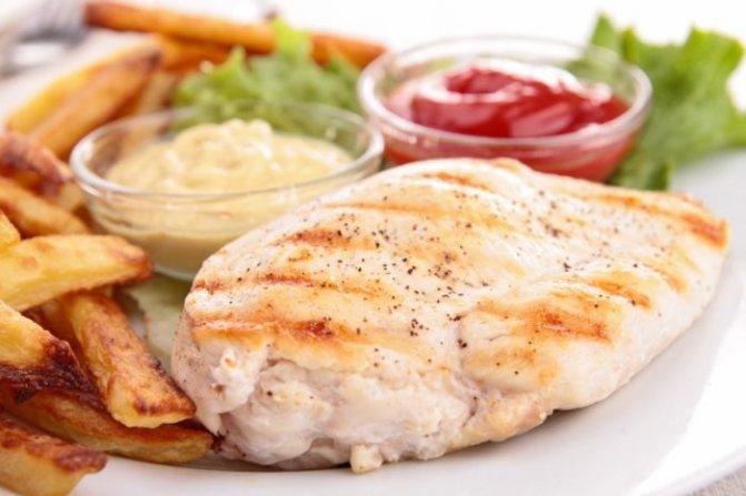 варёная куриная грудка на тарелке с соусами в пластиковых ёмкостях, готовые к упаковке в дорогу